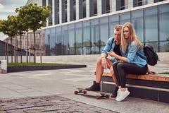 Jeunes couples attrayants heureux dans des vêtements sport se reposant sur un banc contre un gratte-ciel, observant quelque chose Image libre de droits