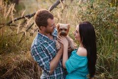 Jeunes couples attrayants heureux posant avec leur chien - terrier de Yorkshire sur la nature Images stock
