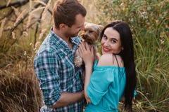 Jeunes couples attrayants heureux posant avec leur chien - terrier de Yorkshire sur la nature Photos stock