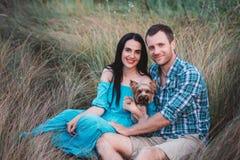 Jeunes couples attrayants heureux posant avec leur chien - terrier de Yorkshire sur la nature Photo stock