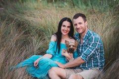 Jeunes couples attrayants heureux posant avec leur chien - terrier de Yorkshire sur la nature Image stock