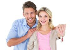 Jeunes couples attrayants montrant la clé de nouvelle maison Photos stock