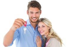 Jeunes couples attrayants montrant la clé de nouvelle maison Photographie stock