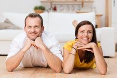 Jeunes couples attrayants paresseux déroulant à la maison Image stock