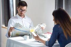 Jeunes couples attrayants prenant le petit déjeuner et lisant les nouvelles dans la salle à manger de l'hôtel photos libres de droits