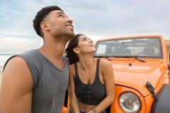 Jeunes couples attrayants recherchant tout en se tenant près d'une voiture Image libre de droits