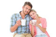 Jeunes couples attrayants se reposant tenant des tasses Images libres de droits