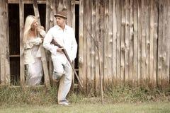 Jeunes couples attrayants se tenant ensemble contre le mur en bois de grange Images stock