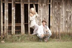Jeunes couples attrayants se tenant ensemble contre le mur texturisé de grange Image stock