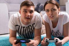 Jeunes couples attrayants se trouvant sur une couverture jouant des jeux vidéo Photo stock