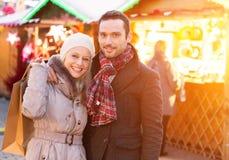 Jeunes couples attrayants sur un marché de Noël Photos stock