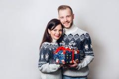 Jeunes couples attrayants tenant le cadeau au-dessus du fond blanc Images libres de droits