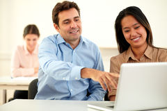 Jeunes couples attrayants travaillant sur l'ordinateur portable Photos stock