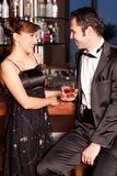 Jeunes couples au bar buvant et flirtant Photos libres de droits