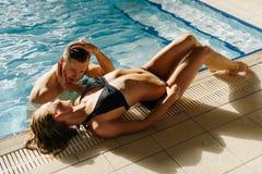 Jeunes couples au bord de la piscine Équipez regarder la femme la fille que sexy a arrosé ses cheveux et a mis la main sur la têt Images stock