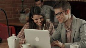 Jeunes couples au café regardant l'ordinateur portable et fumant le narguilé Photo stock