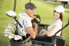 Jeunes couples au chariot de golf Image stock