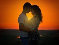 Jeunes couples au coucher du soleil sur le fond de ciel, concept d'amour, personnes romantiques Photographie stock