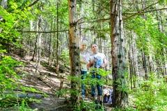 Jeunes couples augmentant avec des sacs à dos dans la forêt Images libres de droits