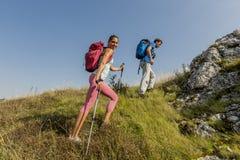 Jeunes couples augmentant sur la montagne images stock