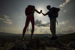 Jeunes couples augmentant sur la montagne photos stock