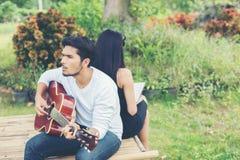 Jeunes couples avec du charme dans l'amour jouant la guitare acoustique dans le pair Photographie stock libre de droits