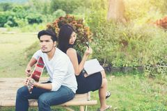 Jeunes couples avec du charme dans l'amour jouant la guitare acoustique dans le pair Photos stock