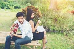 Jeunes couples avec du charme dans l'amour jouant la guitare acoustique dans le pair Images stock