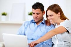 Jeunes couples avec du charme se reposant sur le sofa Photos libres de droits