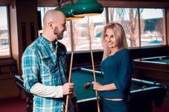 Jeunes couples avec du charme souriant à chaque autres et billard de jeux Image stock