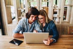Jeunes couples avec du charme utilisant l'ordinateur portable tout en se reposant au café Images stock