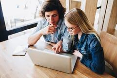 Jeunes couples avec du charme utilisant l'ordinateur portable tout en se reposant au café Photographie stock