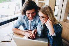 Jeunes couples avec du charme utilisant l'ordinateur portable tout en se reposant au café Photo libre de droits
