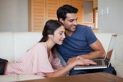 Jeunes couples avec du charme utilisant un ordinateur portatif Photos libres de droits