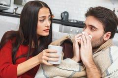 Jeunes couples ayant égaliser à la maison l'amie faisant attention Images libres de droits