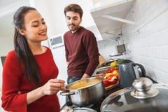 Jeunes couples ayant égaliser romantique à la maison dans la cuisine faisant cuire des pâtes Photographie stock libre de droits