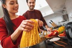 Jeunes couples ayant égaliser romantique à la maison dans la cuisine faisant cuire le plan rapproché de repas ensemble Photographie stock