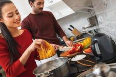 Jeunes couples ayant égaliser romantique à la maison dans la cuisine faisant cuire le repas ensemble Photos libres de droits