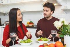 Jeunes couples ayant égaliser romantique à la maison dans la cuisine parlant entre eux Image libre de droits