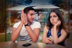 Jeunes couples ayant des problèmes avec leurs téléphones intelligents Image stock