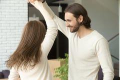 Jeunes couples ayant l'amusement à la maison dansant dans le salon Photos libres de droits