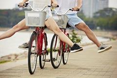 Jeunes couples ayant l'amusement avec des bicyclettes dans le parc Image libre de droits