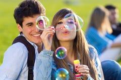 Jeunes couples ayant l'amusement avec des bulles de savon dans le parc photos stock