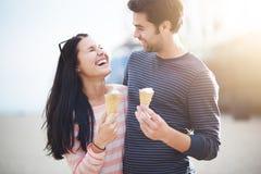 Jeunes couples ayant l'amusement avec des cornets de crème glacée Image libre de droits