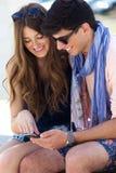Jeunes couples ayant l'amusement avec des smartphones, dehors Photographie stock libre de droits