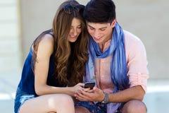 Jeunes couples ayant l'amusement avec des smartphones, dehors Image stock