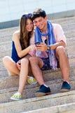 Jeunes couples ayant l'amusement avec des smartphones, dehors Photos stock