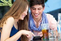 Jeunes couples ayant l'amusement avec des smartphones, dehors Photographie stock