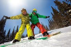 Jeunes couples ayant l'amusement avec des surfs des neiges Photo stock