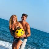 Jeunes couples ayant l'amusement avec la bille sur la plage. Images stock